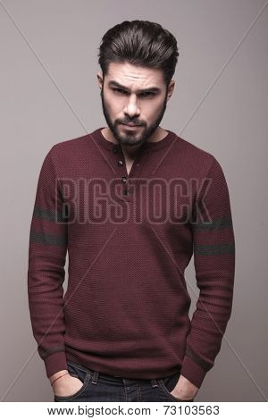Handsome serious man wearing burgundy sweater holding his hands in pocket, looking at the camera