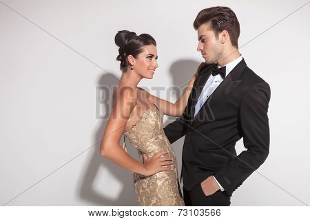 Elegant fashion couple embracing, the man holding one hand in his pocket. Looking at each other.
