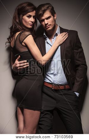 Elegant woman wearing a black dress embracing her lover while he is leaning on a dark grey wall with one hand in his pocket.