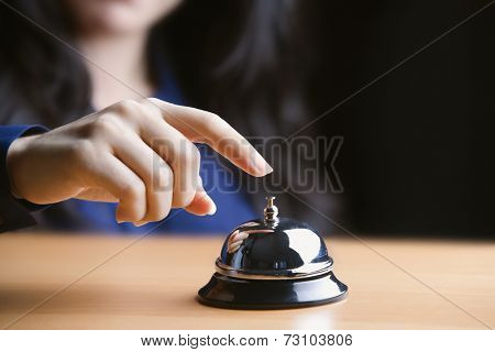Close up of young woman ringing a bell