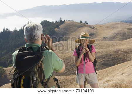 Senior man taking a picture of his wife on a hike