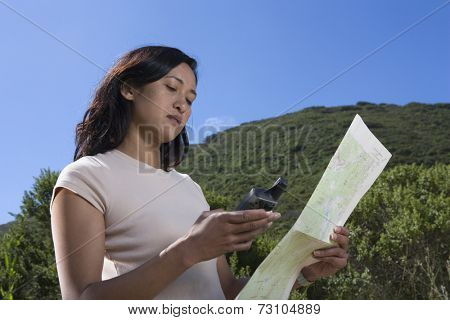 Woman reading map and gaps in forest
