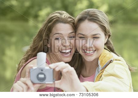 Women taking snapshots in a forest