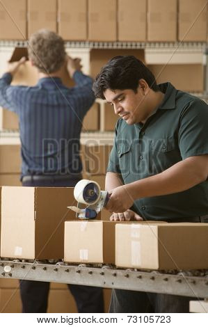 Young man taping a cardboard box closed