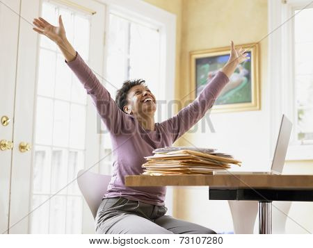 Middle-aged woman celebrating at her desk
