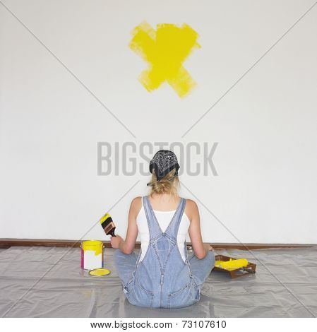 Woman sitting on tarp with paintbrush and paint