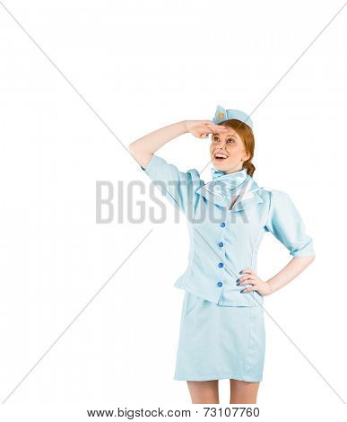 Pretty air hostess looking up on white background