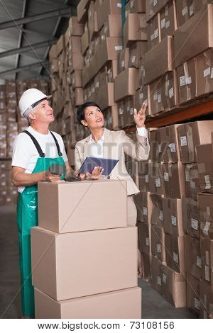 Warehouse worker scanning box with manager holding tablet pc in a large warehouse