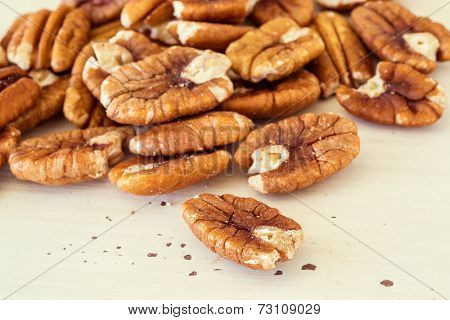 Shelled pecans on a wooden background.