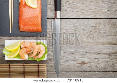 Fresh sea food and kitchen utensils on wooden table with copy space