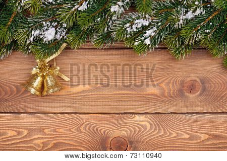 Christmas fir tree with snow and holiday decor on rustic wooden board with paper for copy space