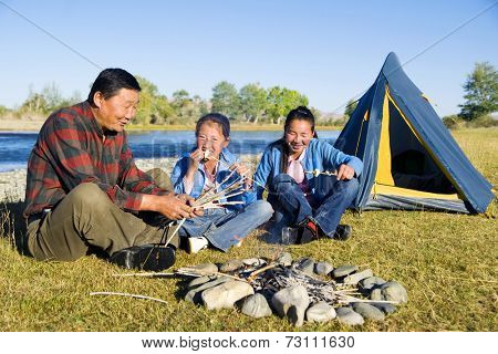 Mongolian family anjoy camping by the river.