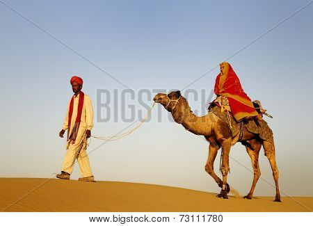 Indigenous Indian man and woman traveling through the desert riding camel.