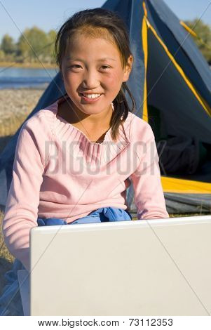 Happy Mongolian girls with laptop at campsite.
