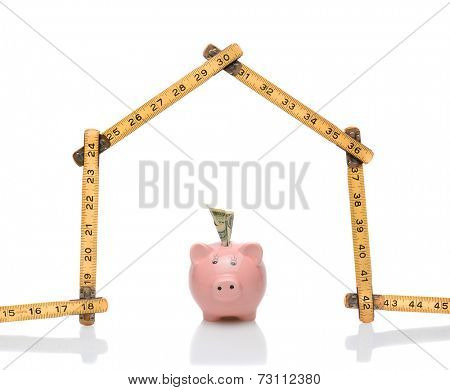 A carpenters ruler in the shape of a house with a piggy bank under the roof. Horizontal format on white with reflections. Great for housing cost and budget concepts.