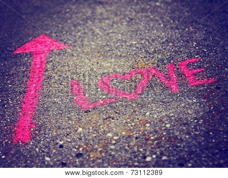 a pink arrow showing the way to love written on a sidewalk with chalk toned with a retro vintage instagram filter effect (very shallow depth of field)