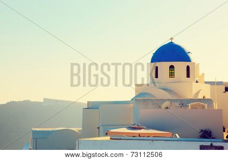 Oia town on Santorini island, Greece at sunset. Traditional and famous church with blue domes over the Caldera, Aegean sea