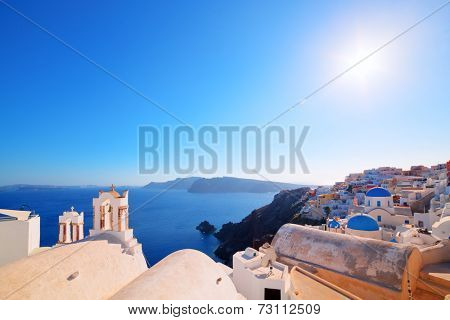 Oia town on Santorini island, Greece. Traditional and famous houses and churches with blue domes over the Caldera, Aegean sea. Wide angle view