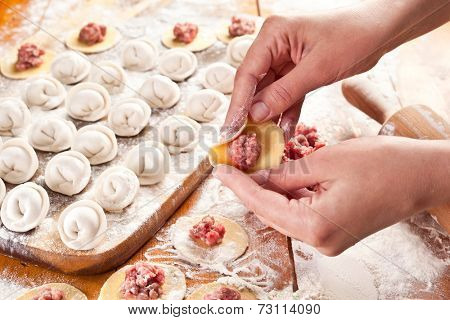 Dumplings. Dough with meat filling on the cook's hands.