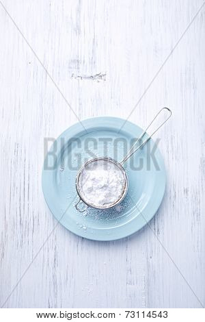 Sieve with icing sugar on a palte
