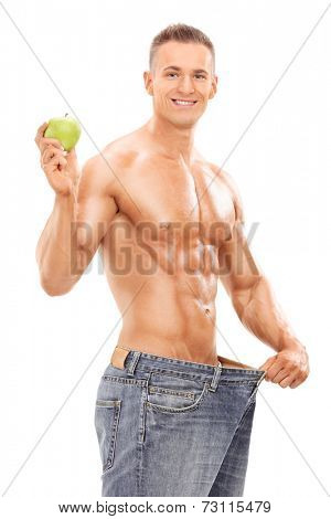 Young man in oversized jeans holding an apple isolated on white background