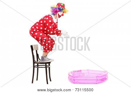 Male clown preparing to jump into a small pool isolated on white background