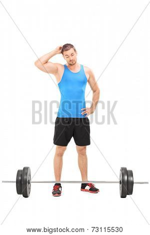 Full length portrait of a doubtful male athlete looking at a barbell isolated on white background