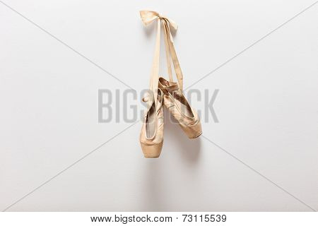 Pair of old silky ballet shoes hanging on a wall