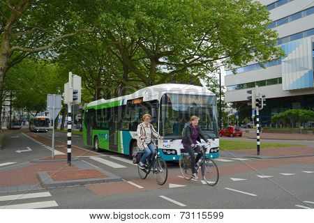 DORDRECHT, NETHERLANDS - JUNE 23, 2013: Women on bikes and the public bus on the Stationsweg street. The Maastricht University calls the bicycle an element of the real Dutch life