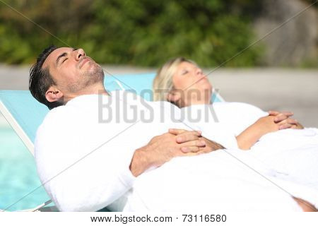 Couple relaxing by luxury hotel swimming-pool