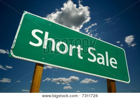Short Sale Green Road Sign Over Clouds