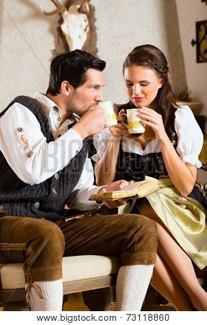 Couple in a traditional mountain hut with fireplace drinking coffee or tea
