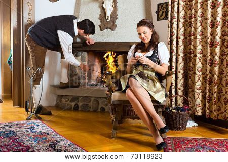 Couple in a traditional mountain hut with fireplace