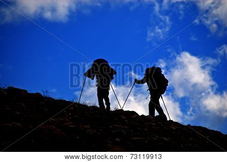 Silhouette of people hiking on mountainside with clouds in sky