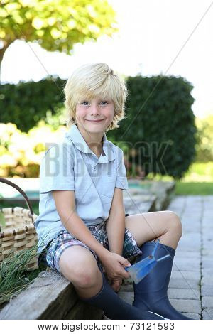Portrait of cute 7-year-old boy in vegetable garden