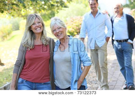 2 generation family walking together in park