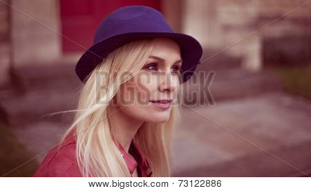 Young blond woman in a trendy hat standing looking off to the right of the frame with a quiet smile on her face