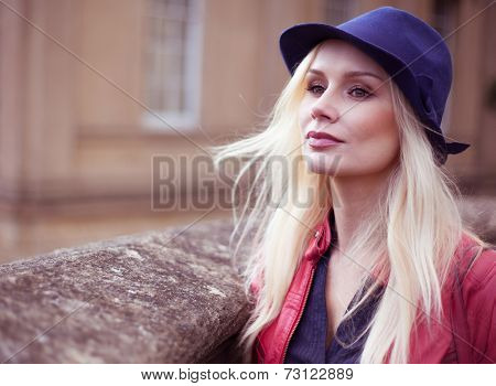 Stylish young blond woman waiting outdoors with her long hair blowing in the breeze leaning against a stone wall looking off to the left of the frame