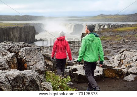 Hiking people in Iceland nature landscape with Selfoss waterfall. Hikers walking with view of famous Icelandic tourist attraction destination in Vatnajokull national park.