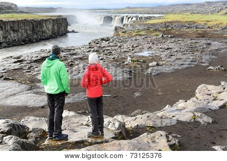 Iceland nature landscape with people by Selfoss waterfall. Hikers enjoying view of famous Icelandic tourist attraction destination. Hiking couple taking break by Selfoss in Vatnajokull national park.