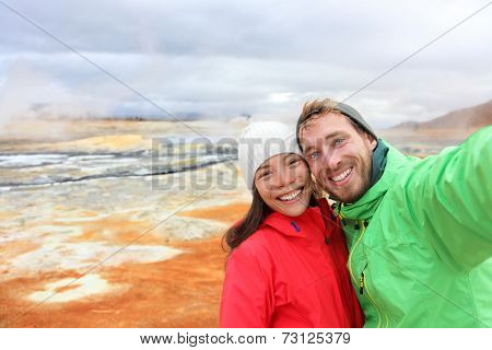 Iceland tourists couple taking selfie photo with smartphone camera at landmark destination: Namafjall Hverarondor hverir mudpot also called mud pool hot spring or fumarole. Beautiful Icelandic nature.