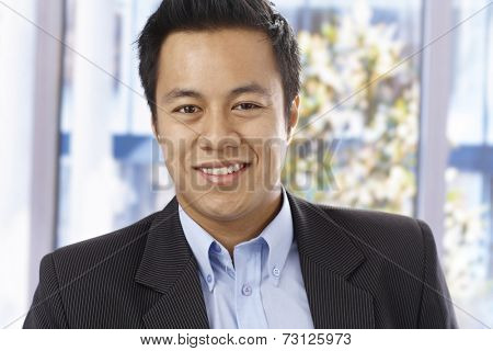 Closeup portrait of handsome young businessman, smiling, looking at camera.