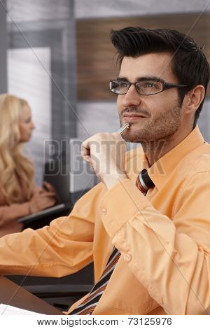 Young businessman daydreaming in office, smiling.