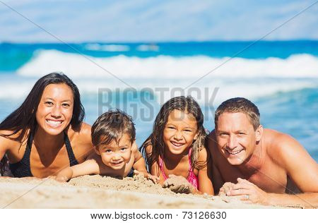 Happy Mixed Race Family of Four Playing and Having Fun on the Beach in the Sand. Tropical Beach Family Vacation.
