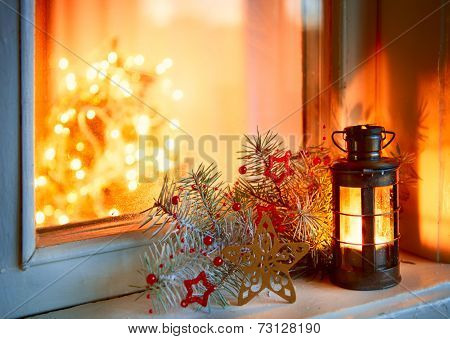 Christmas lantern in night on old window.