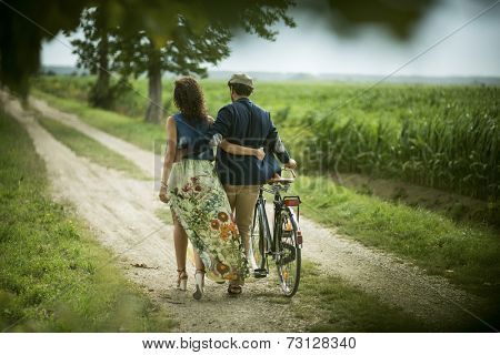 Rear view of a happy couple walking holding bike