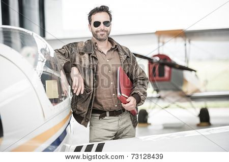 Pilot standing next to his airplane