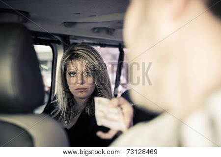 Young woman paying for the taxi in cash