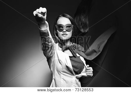 Young pretty woman opening her shirt like a superhero. Super girl, image toned. Beauty saves the world. Black and white.