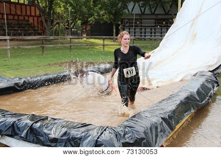 MUSKOGEE, OK - Sept. 13: A woman slides into a muddy pit to avoid zombies during the Castle Zombie Run at the Castle of Muskogee in Muskogee, OK on September 13, 2014.